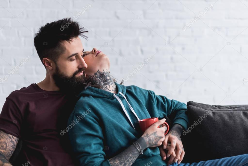 tattooed couple sitting on sofa with cup of coffee