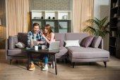 Mladý pár sedící na gauči a čtení kniha v obývacím pokoji