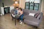 Vysoký úhel pohled šťastný pár sedí na gauči a používat přenosný počítač v obývacím pokoji v moderním designu