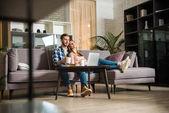 Povrchové úrovni zobrazení páru sledoval přenosný počítač v obývacím pokoji s moderním interiérem