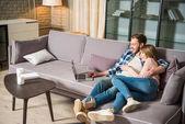 Šťastný pár objímaly a Bavíte se s notebooky v obývacím pokoji