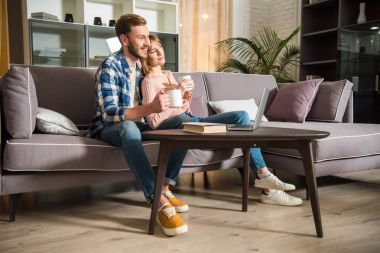Side view of male with girlfriend sitting on couch with cups and watching laptop in modern living room