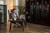 Muž sedí v křesle a používat přenosný počítač v obývacím pokoji s designovým interiérem