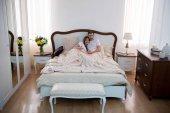 Fotografie Vysoký úhel pohledu šťastnému páru objímání v útulné moderní ložnici