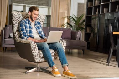 Young male in armchair using laptop in living room with modern design