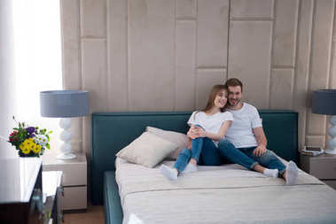 Happy couple sitting on bed with pillows in bedroom with modern interior