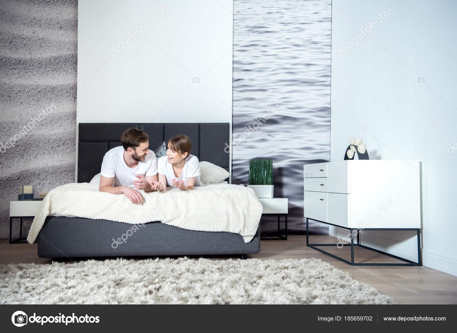 Lachende paar praten liggend bed gezellige slaapkamer met modern