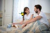 Fotografie Usmívající se pár sedí na posteli se snídaní na zásobník v pokoji s moderním interiérem