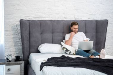 Happy young male using laptop in cozy modern bedroom