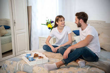 Couple on bed with breakfast on tray in cozy bedroom