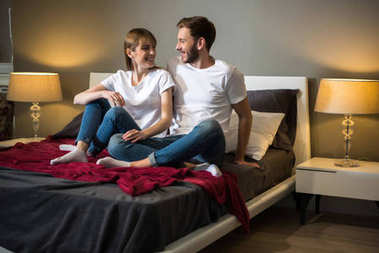 Happy young couple sitting on bed in cozy modern bedroom