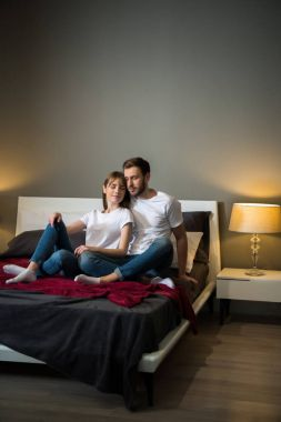Couple sitting with closed eyes in bedroom with modern interior