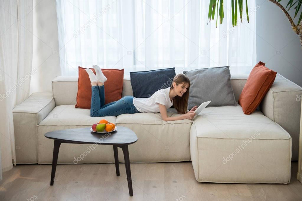 Side view of young female lying on couch and using digital tablet in living room with modern interior