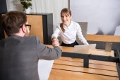 Fotografie Business colleagues shaking hands of each other at workplace