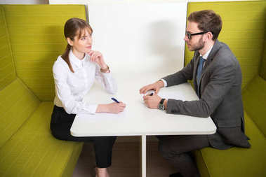 Business colleagues having meeting at table with pens in hands