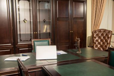 Interior of office room with laptop, statuette and papers on table
