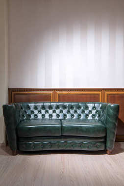 Green leather couch in front of wall with wooden decoration