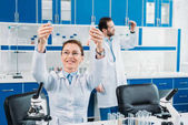 Fotografie selective focus of female researcher looking at tubes with reagents in hands with colleague behind in lab