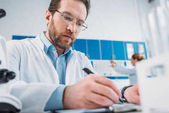 Fotografie selective focus of scientist in white coat and eyeglasses making notes in notepad at workplace in laboratory