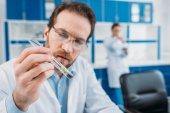 szelektív összpontosít tudós fehér kabátot és szemüveg nézte csövet a kezében laboratóriumi reagens
