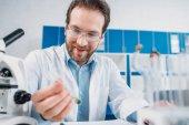 Selektivní fokus usmívající se vědec v bílém plášti a brýle s činidlem v ruce v laboratoři při pohledu na baňky