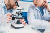 a tudományos kutatók fehér szőrű együtt dolgoznak a munkahelyen Mikroszkóp laboratóriumban részleges megtekintése
