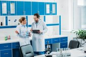 Photo scientific researchers in white coats and eyeglasses with flasks and notepad in laboratory