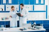 vědců v bílých pláštích a brýle s Poznámkový blok v laboratoři