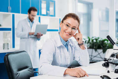 selective focus of smiling female scientist in eyeglasses at workplace with colleague behind in lab