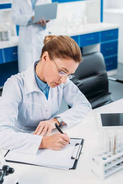 selective focus of female scientist making notes in notepad with colleague behind in lab