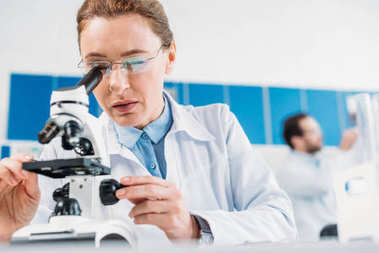 selective focus of female scientist looking thorough microscope on reagent with colleague behind in lab