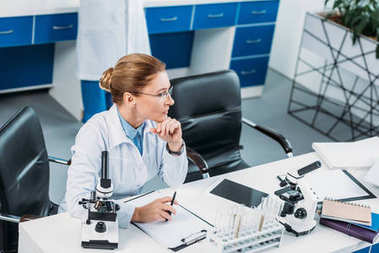 selective focus of pensive female researcher at workplace with colleague behind in lab