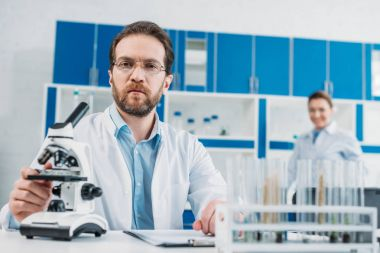 selective focus of scientist in white coat and eyeglasses at workplace with microscope in laboratory