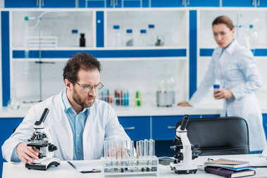selective focus of scientist in white coat and eyeglasses at workplace with microscope and colleague behind in laboratory