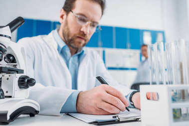 selective focus of scientist in white coat and eyeglasses making notes in notepad at workplace in laboratory