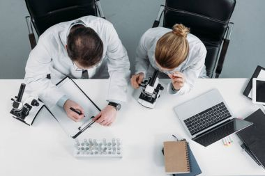 overhead view of scientific researchers in white coats working together at workplace in laboratory
