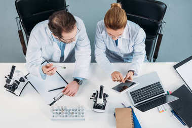 overhead view of scientific researchers in white coats using tablet together at workplace in laboratory