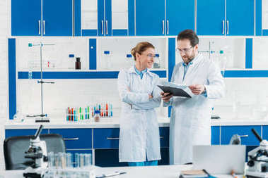 scientific researchers in white coats and eyeglasses with notepad in laboratory