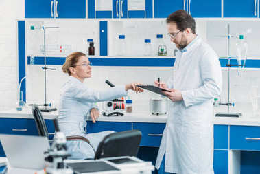 scientific researchers in white coats and eyeglasses working together in laboratory