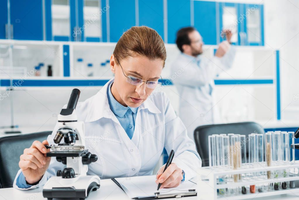 selective focus of female scientist making notes in notepad at workplace with colleague behind in lab
