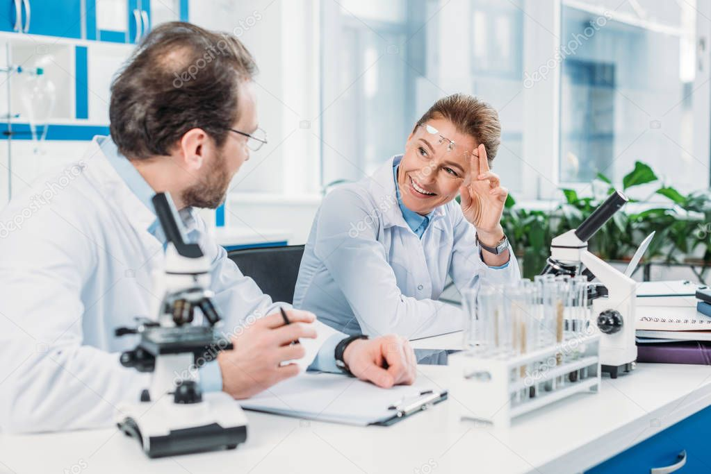 scientific researchers in white coats working together at workplace in laboratory