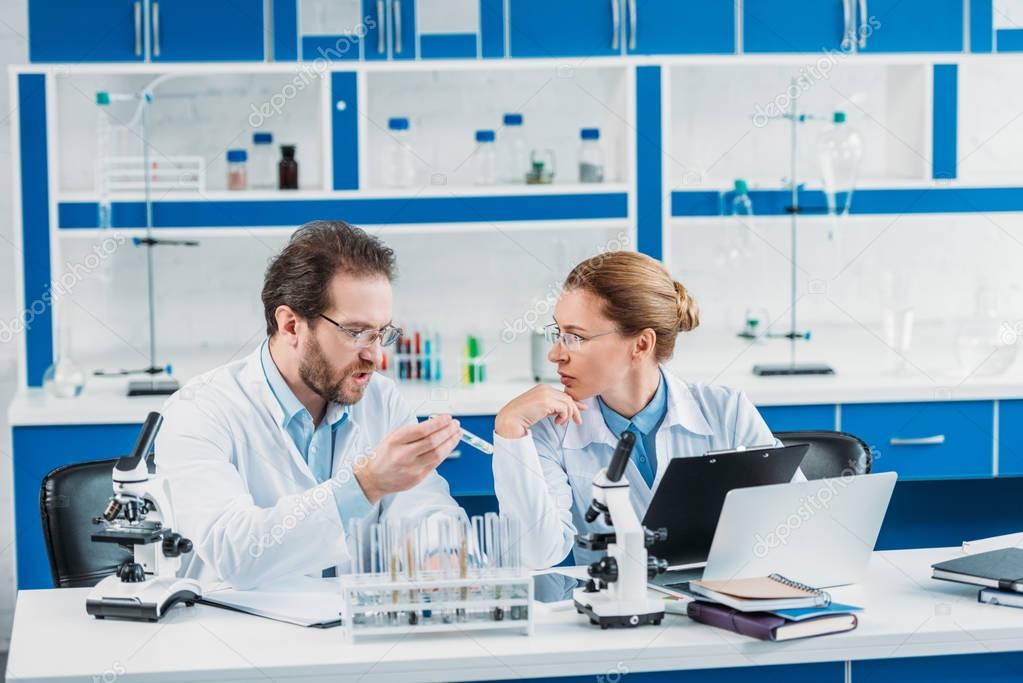 Portrait of scientific researchers in white coats at workplace with flasks, microscopes and laptop in laboratory stock vector