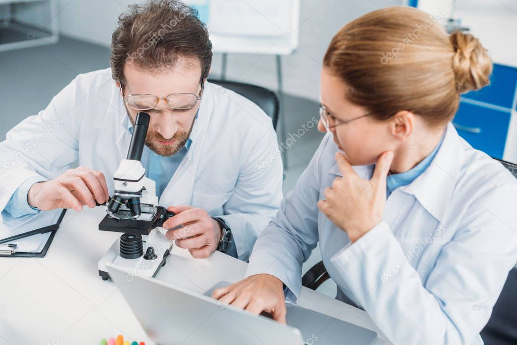 portrait of scientific researchers in white coats working together at workplace with microscope  in laboratory