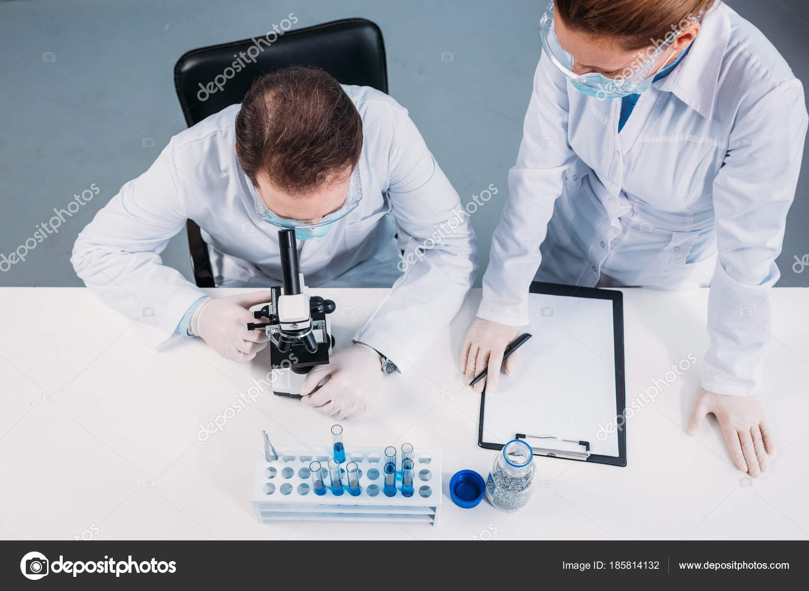 Vue aérienne de scientifiques médicaux masques et lunettes de travail sur  la recherche scientifique en laboratoire — Image de VitalikRadko b58e96c40f6d