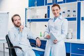 portrét vědeckých výzkumníků v laboratorní pláště s digitálním tabletu v laboratoři