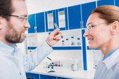 boční pohled vědců v brýlích s trubicí s činidlem v laboratoři