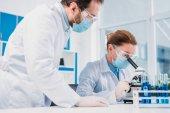 Fotografia ricercatori in camice bianco e maschere medico lavora con reagenti insieme in laboratorio