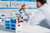 Selektive Fokussierung von Röhrchen mit Reagenzien und Wissenschaftlern am Arbeitsplatz im Labor