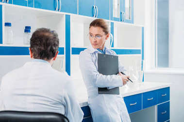partial view of female scientist with notepad in hands standing near colleague in lab
