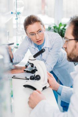 selective focus of scientists in eyeglasses working together at workplace with microscope in laboratory